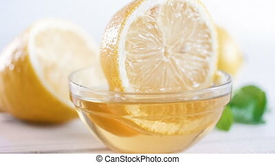 Closeup slow motion footage of lemon dipping and taking out...