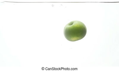 Closeup slow motion footage of one fresh ripe apple falling...