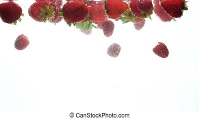 Closeup slow motion footage of red ripe berries floating and...