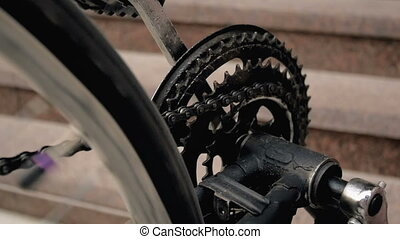 Closeup slow motion footage of rotating pedals, chain and wheel of old bicycle