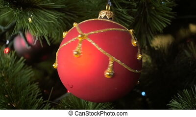 Closeup slow motion footage of rotating red bauble on...