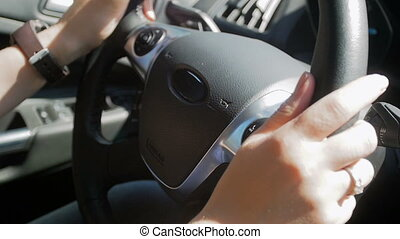 Closeup slow motion footage of woman holding steering wheel...