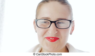 Closeup slow motion video of beautisul smiling woman wearing eyeglasses looking in camera