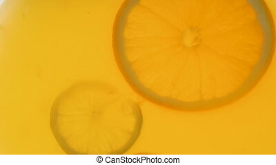Closeup slow motion video of citrus fruits slices floating in orange juice