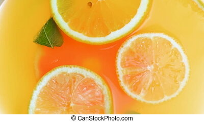 Closeup slow motion video of cold lemonade with oranges,...