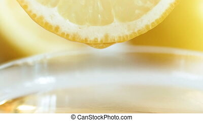 Closeup slow motion video of droplet of juice falling from lemon slice in gla