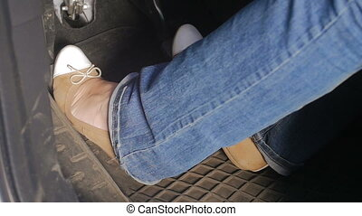 Closeup slow motion video of female driver pressing pedals...