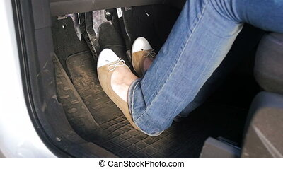 Closeup slow motion video of female drivers feet pressing...
