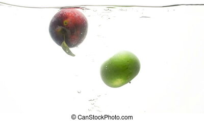 Closeup slow motion video of fresh green and red apple falling in cold water against white background