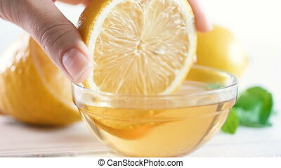 Closeup slow motion video of hand slowly dipping lemon in...