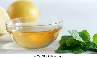 Closeup slow motion video of honey jar, mint and lemons on...