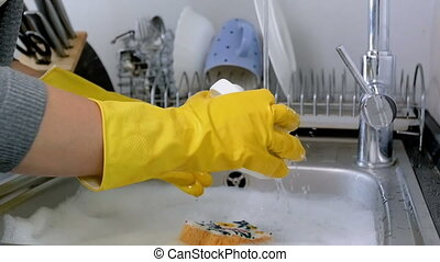 Closeup slow motion video of housewife in rubber gloves washing dishes on kitchen
