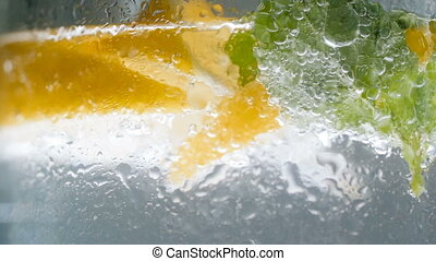 Closeup slow motion video of misty wet glass of lemonade -...