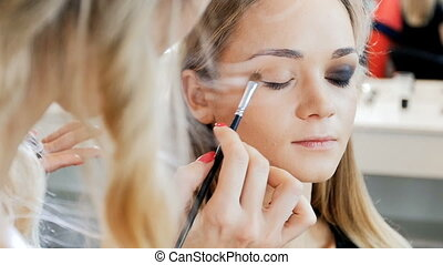 Closeup slow motion video of professional makeup artist...