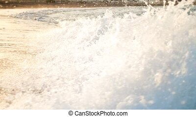 Closeup slow motion video of sea waves flowing on sandy beach