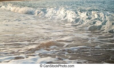 Closeup slow motion video of sea waves flowing on sandy...