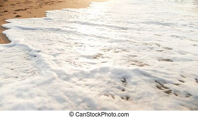 Closeup slow motion video of sea waves washing off...