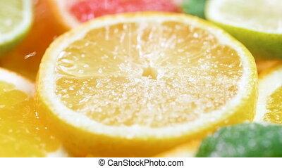 Closeup slow motion video of sugar fallling on freshly cut lemon slice