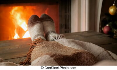 Closeup slow motion video of woman warming feet at fireplace...