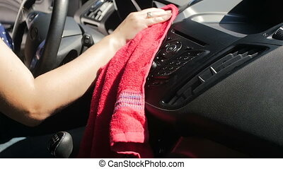 Closeup slow motion video of young woman cleaning her car...