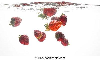 Closeup slow mtoion video of fresh ripe strawberries falling...