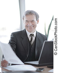 smiling senior businessman sitting at his Desk
