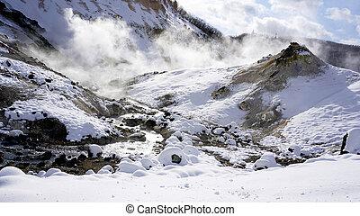 Closeup snow stone and stream in the mist Panorama Noboribetsu onsen