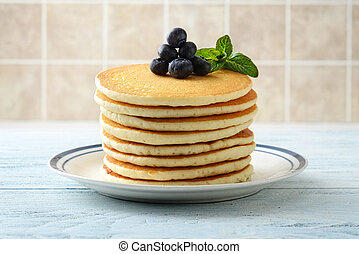 closeup stack of pancakes with blueberries and mint