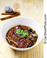 Closeup stewed pork leg in gravy soup and herb on wood table