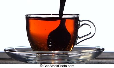 Closeup. Tea spoon stir the drink in a glass cup