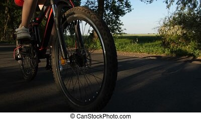 Closeup teen legs and bike wheels riding on road