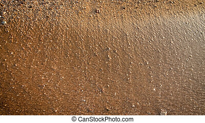 Closeup texture of wet sand and small rocks on the beach at sunset