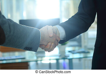 closeup .the financial partners shaking hands over a Desk
