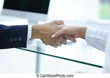 closeup .the financial partners shaking hands over a Desk .