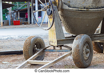 closeup the wheels of cement mixer on the construction site, horizontal photo.