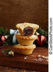 closeup three mincemeat pies with christmas decorations