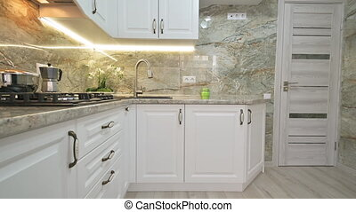 Ultra wide angle closeup up to down tilt camera movement of modern classic white kitchen interior with furniture and appliances