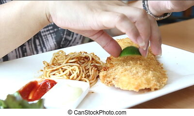 closeup to deep fired fish steak eating on white plate