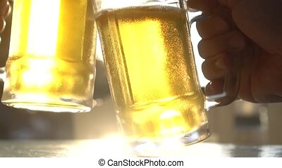 Closeup toast clinking lager beer glasses mugs with sun rays...