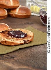 closeup toasted hot cross bun with jam