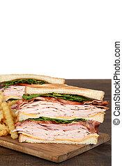 closeup toasted turkey club sandwich with fries