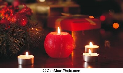 Closeup toned 4k footage of burning candle on wooden table decorated for Christmas eve. Perfect background or backdrop for Christmas or New Year