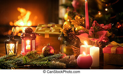 Closeup toned image of Christmas decorations on wooden table against burning fireplace