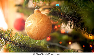 Closeup toned photo of beautiful sprakling Chrismtas tree bauble hanging on branch against sun rays shining through big window