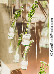 toned photo of decorated bottles with flowers hanging on...