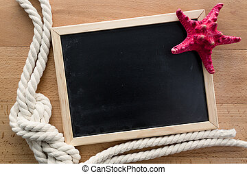 toned photo of empty blackboard with starfish and marine knot
