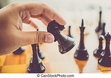 toned photo of man making move with black horse at chess ...