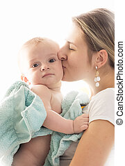 Closeup toned portrait of young loving mother kissing her baby son covered in blue towel after having bath