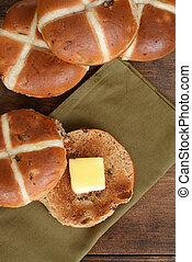 top view hot cross bun with butter on green napkin