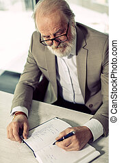closeup top view photo of grey-headed senior writer with pen...